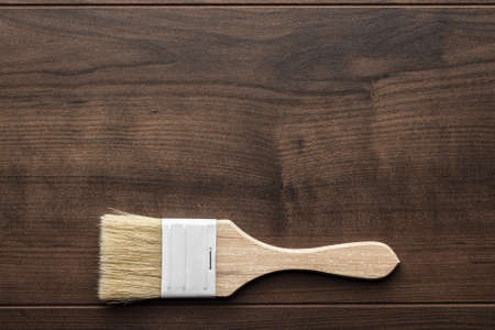 refurbishing: paint brush on the brown wooden table