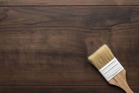 refurbishing: new paint brush on the brown wooden table background