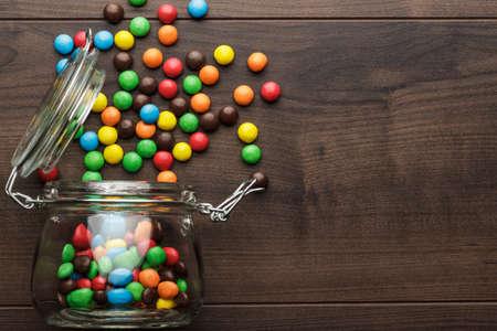 Omvallen glazen pot vol met kleurrijke snoepjes Stockfoto - 34606854