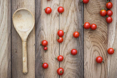 cherry tomatoes and wooden spoon on the table photo