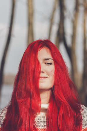 redhaired: beautiful red-haired woman smiling portrait near the river