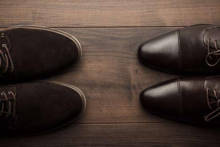 木製のテーブルの上の茶色の靴の 2 つのペア