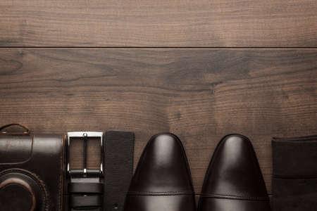 brown shoes, socks, belt, and film camera on wooden table Standard-Bild