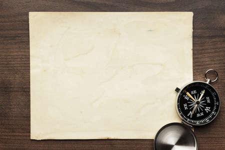 brujula antigua: comp�s y papel viejo en el fondo de la tabla de madera marr�n