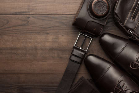 bruine schoenen, sokken, riem, en filmcamera op houten tafel Stockfoto