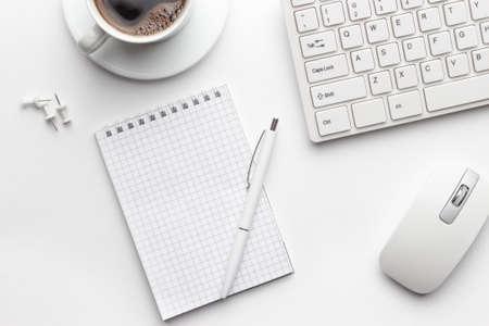 bekijken van bovenaf op wit kantoor tafel met notitieblok, computer en koffiekopje