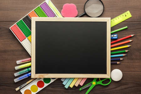 back to school supplies: school supplies and blackboard with copy space on the table
