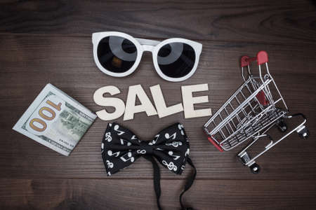 sale concept on the wooden background. shopping trolley photo