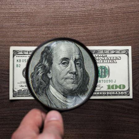 dinero falso: autenticaci�n del billete de cien d�lares en el fondo de madera Foto de archivo