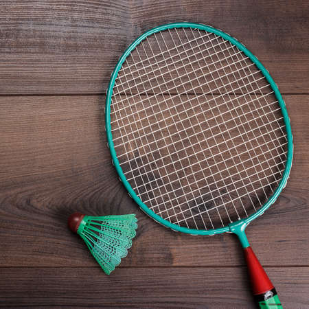 badminton racket: shuttlecock and badminton racket on wooden table after the game