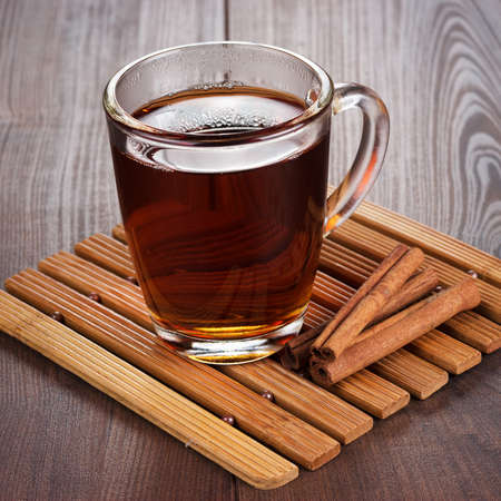 teacup with hot tea and cinnamon sticks on the dining table photo