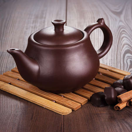 teapot with hot tea and cinnamon sticks on the dining table photo