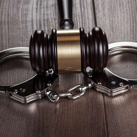 swindler: handcuffs and judge gavel on brown wooden table background Stock Photo