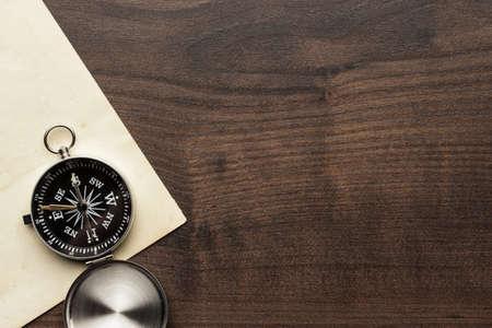 kompas en oud papier op de bruine houten tafel achtergrond