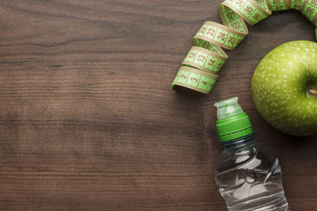 bottle of water, measuring tape and fresh green apple on the wooden table Standard-Bild