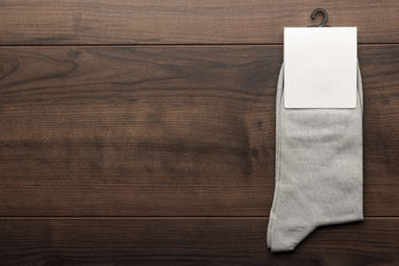 men socks: pair of gray socks with blank packing on the wooden table