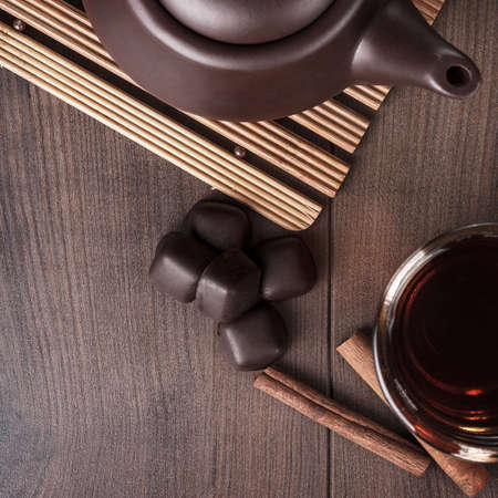 trivet: cup of tea with cinnamon sticks and sweets on the table Stock Photo