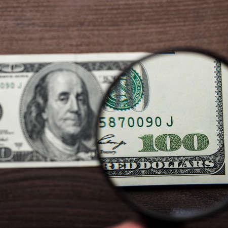 dinero falso: cien dólares autenticidad de los billetes en el fondo de madera