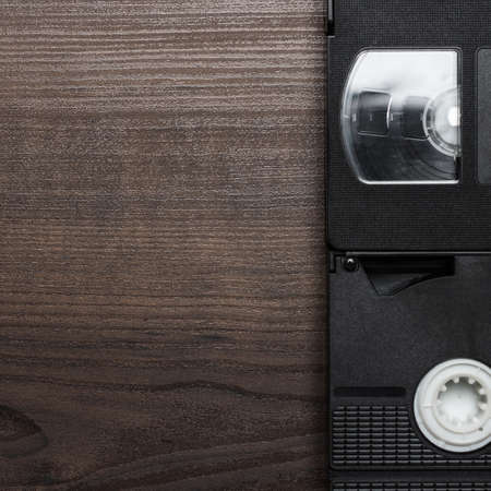 videocassette: old retro video tapes over brown wooden background