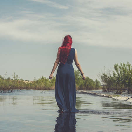 shallow water: red-haired woman walking in the river shallow water