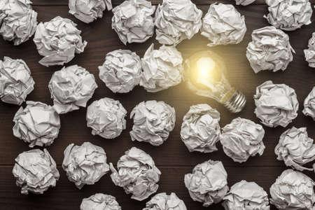 しわくちゃの事務用紙と電球の新しいアイデア コンセプト