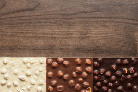 chocolate bars: black, milk and white chocolate bars with whole hazelnuts on wooden table
