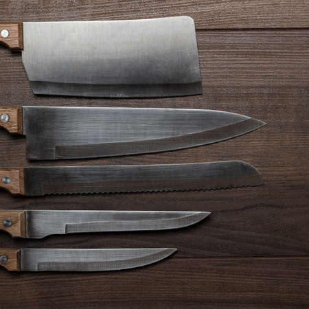 stainless steel kitchen: five kitchen knifes on the brown wooden