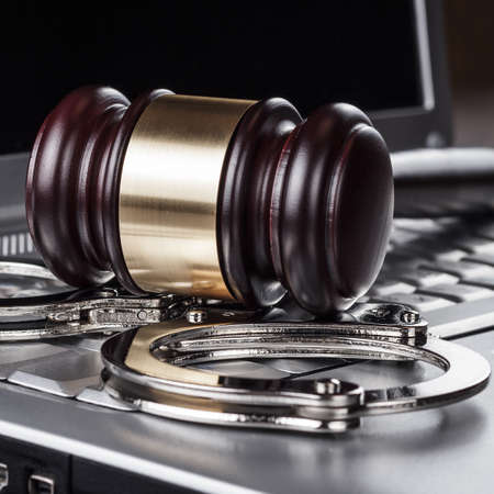 computer crime: handcuffs and judge gavel on computer cyber crime concept