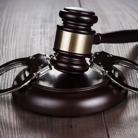 wristlets: handcuffs and judge gavel on the brown wooden table Stock Photo