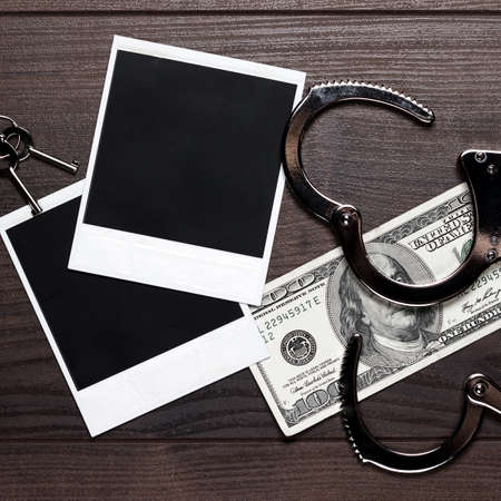 control fraud: handcuffs money and old photos on wooden table detective concept