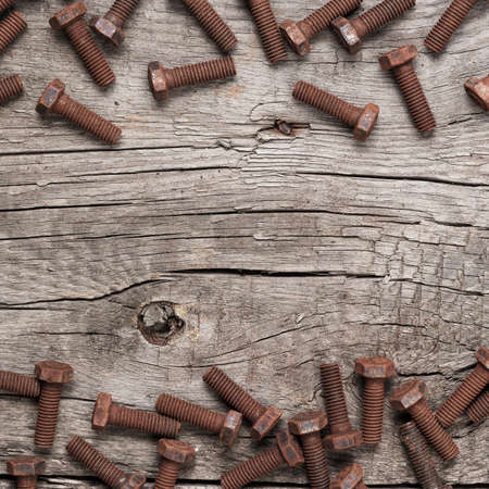 gudgeon: old rusty screw bolts on the wooden table