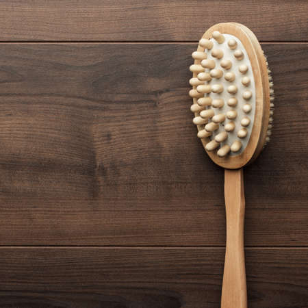 massager: wooden massager brush on the brown table