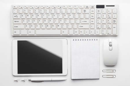 overhead of essential office objects in order on white desk. notebook, computer keyboard and mouse, tablet pc, pen, push pins, paper clips Stock Photo