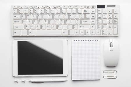 Overhead van essentiële kantoor objecten om op wit bureau. notebook, toetsenbord en muis, tablet pc, pen, push pins, paperclips Stockfoto - 36780799