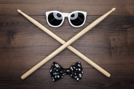 drum sticks: pair of wooden drumsticks crossed on wooden table, sunglasses and bow tie Stock Photo