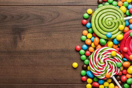 caramelos: diferentes dulces de colores y piruletas en la mesa de madera Foto de archivo
