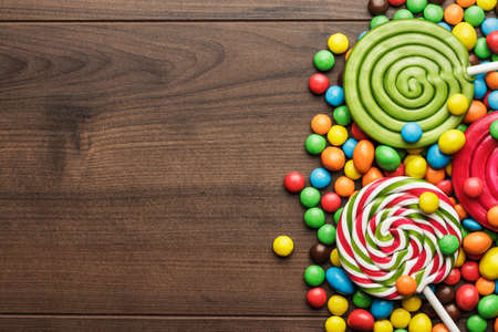 different colorful sweets and lollipops on the wooden table