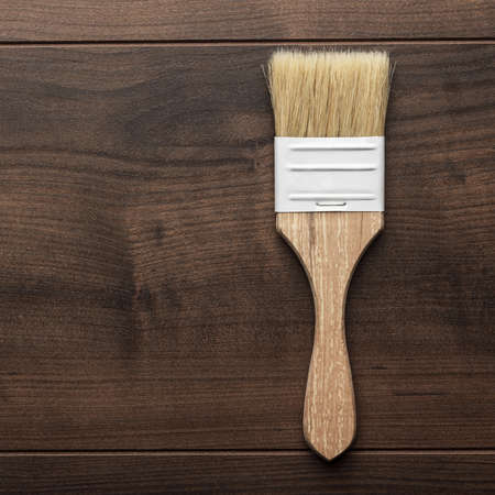 repaint: paint brush on the brown wooden table
