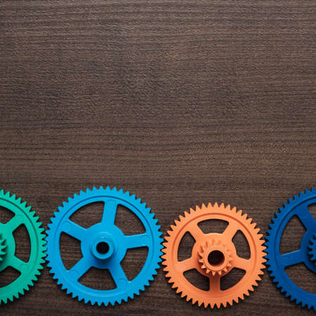 clockwork: colorful gears on the brown wooden background