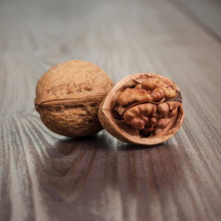 two walnuts on the brown wooden table background
