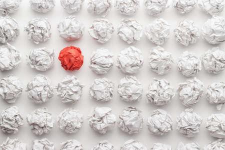 overhead schot van verfrommeld papier in oder en rode een staande uit. geweldig idee concept op de witte kantoor tafel