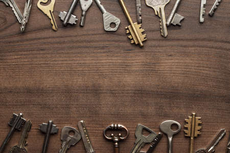 many different keys on brown wooden background with copy space in the centre Фото со стока