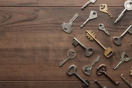many different keys on brown wooden background with copy space Banque d'images