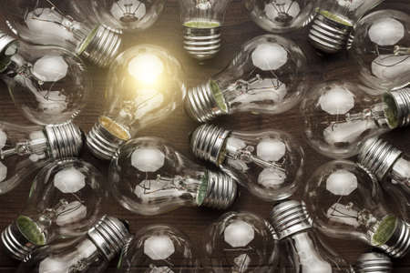uniqueness: glowing bulb uniqueness concept. many bulbs on brown wooden table