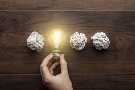 lluvia de ideas: nueva idea de concepto con papel de oficina arrugado, mano femenina que sostiene la bombilla