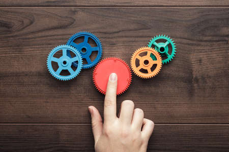 challenging: perfect solution concept. colorful gears and hand on the brown wooden background