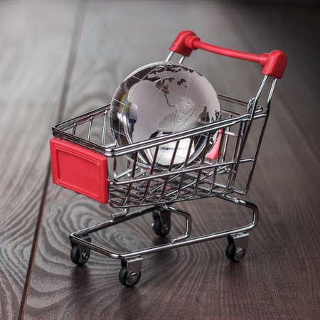 carretilla de mano: globo de cristal en el concepto de mercado mundial carrito de la compra