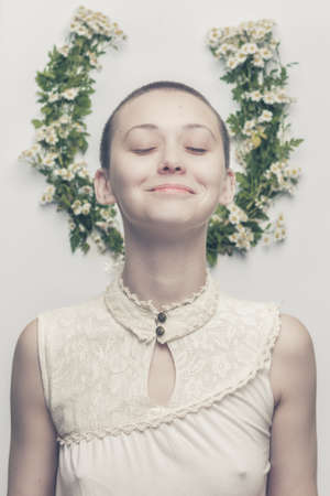 butch: portrait of beautiful smiling bald-headed girl over floral background Stock Photo