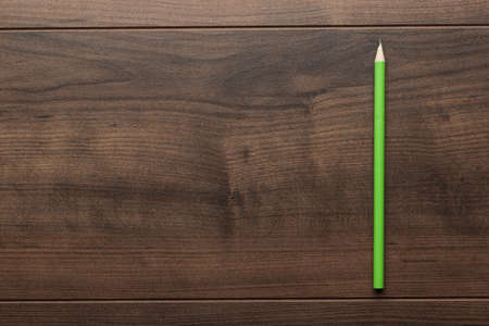 green pencil on the brown wooden table