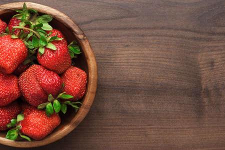 frutilla: cuenco de madera lleno de fresas frescas en la mesa de color marrón Foto de archivo